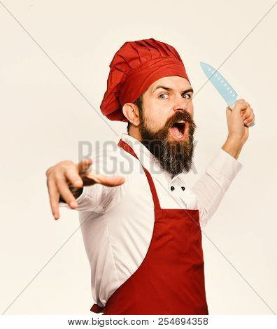 Chef pretends to throw sharp blue knife. Cooking and professional culinary concept. Man with beard in cook uniform isolated on white background. Cook with angry face in burgundy apron and chef hat. poster