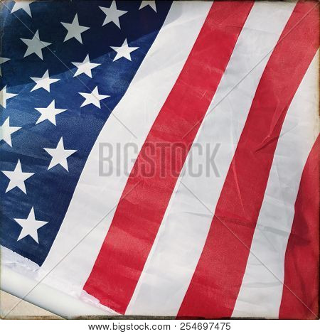 Filtered image of an American flag waving in a suburban neighborhood - USA flag for 4th of July Independence Day, Labor Day, Veterans Day, Memorial Day, Patriotic