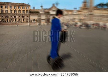 Abstract Background. The Guy Crosses The Square On The Segway. Blur Effect Defocusing Filter Applied