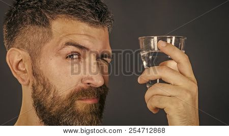 Life source and healthcare. Hangover and thirst. Hipster drink clean healthy water, refreshing. Health and dieting. Man with long beard hold water glass on grey background. poster