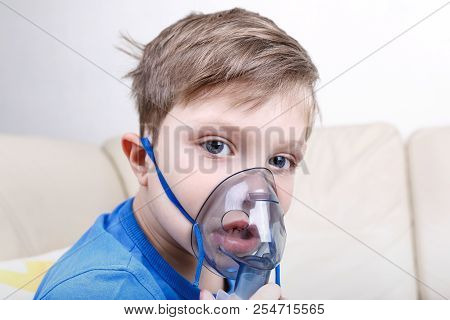 Sick Chid With Pediatric Nebulizer Looking At Camera