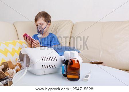 Boy breathe through nebulizer. Sick chid with pediatric nebulizer. poster