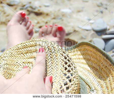Two foots and one arm on the beach with hat