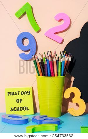 a pencil pot with pencil crayons of different colors, some three-dimensional numbers of different colors and the text first day of school written in a yellow sticky note, against a pink background