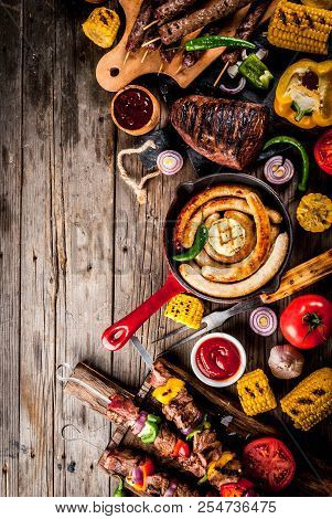 Assortment various barbecue food grill meat, bbq party fest - shish kebab, sausages, grilled meat fillet, fresh vegetables, sauces, spices, on old wooden rustic table, above copy space poster