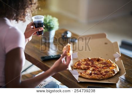 woman eating pizza and drinking cola while sitting on sofa watching tv in home late at night