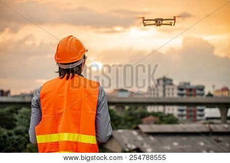 Young Asian Engineer Man Flying Drone Over Construction Site During Sunset. Using Unmanned Aerial Ve