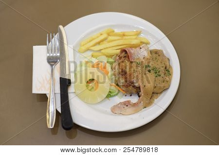 Grilled Chicken And Bacon With Black Pepper Sauce, Carrot, Pineapple And French Fries Serve On White