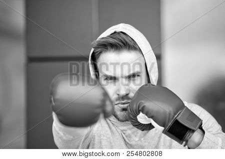 Boxing Concept. Man Athlete On Concentrated Face With Sport Gloves Practicing Boxing Punch, Urban Ba