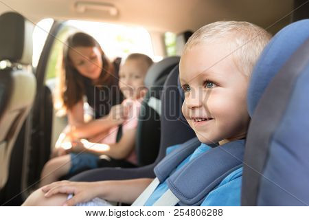 Boys Buckled Into Car Seat. Mother Takes Care About Her Children In A Car. Safe Family Travel Concep