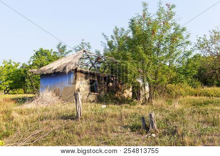 Old Ruined Rural House With Broken Thatched Roof. Traditional Rural Landscape. Unnecessary, Ruined,