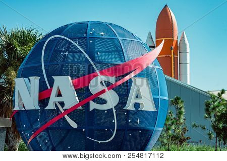 Cape Canaveral, Florida - August 13, 2018: Nasa Globe With Space Shuttle Booster Rocket In Backgrond