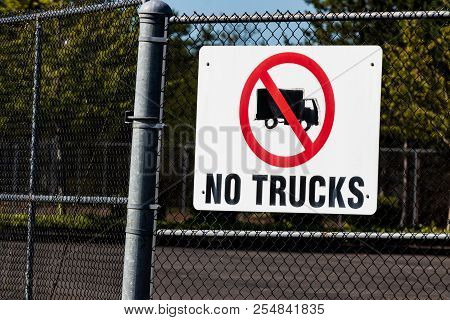 White No Trucks Sign On A Chain Link Fence Gate