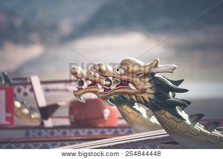 A Row Of Dragon Boats With The Traditional Figureheads