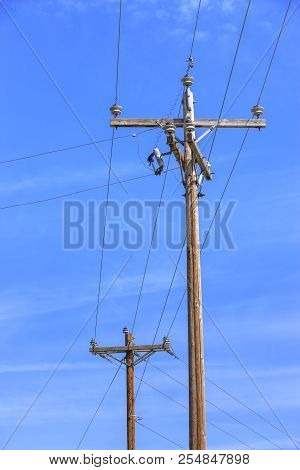 Telephone Poles And Power Lines. Conceptual Image Of Telephone Pole And Wires Against A Blue Sky.