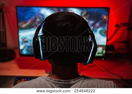 Portrait from back of young gamer guy looking at screen and playing video games on computer in dark room wearing headphones