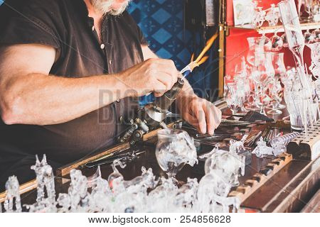 Hands Of The Handicraftsman Making A Glass Subject At Fair Of Crafts. The Master Of Glass Blowers Wo