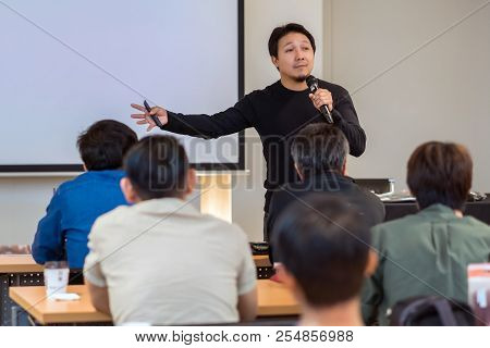 Asian Speaker With Casual Suit On The Stage In Low Light Over The Presentation Screen In The Busines