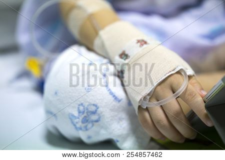 Sick child on a receiving a saline solution in hospital poster