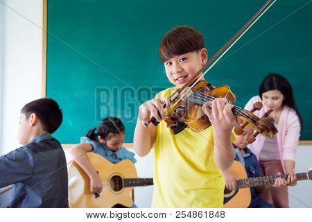 Young Asian Boy Smiling While Playing Violin In Music Class At School