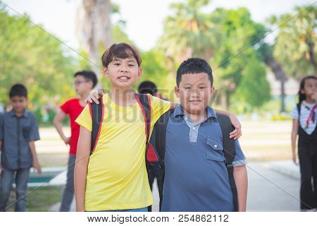 Young Asian Boys Friend Standing In Park And Smiling At Camera