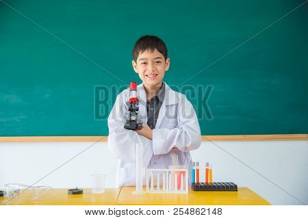 Litlle Asian Boy Wearing White Coat And Holding Microscope Smiling In Front Of Classroom