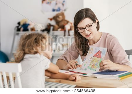 A Professional Child Education Therapist Having A Meeting With A Kid In A Family Support Center.