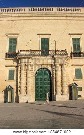 Valletta, Malta - May 2018: Man Walk In Valletta Along Close Big Green Gate Of Grandmaster Palace In