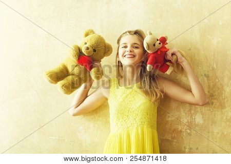 Pretty Girl Or Cute Smiling Woman With Blond Hair And Adorable Happy Face In Yellow Dress With Teddy
