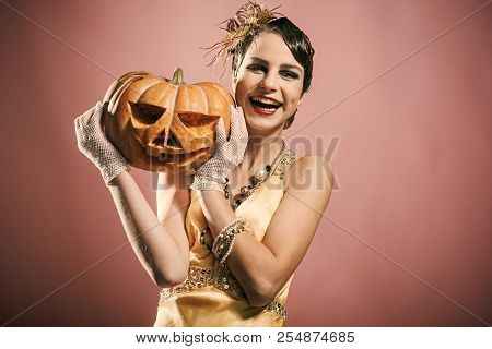Halloween Holiday And Party Celebration. Halloween Girl In Yellow Dress With Pumpkin. Beauty And Vin