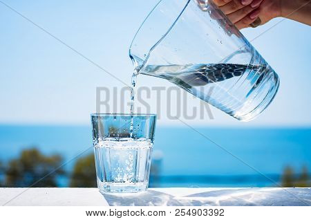 A Glass Of Water Against The Background Of The Sea. A Woman's Hand Pours Water Into A Glass.