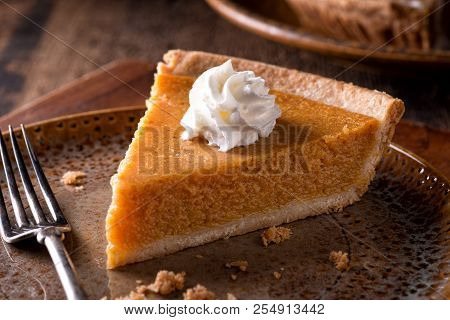 A Slice Of Delicious Home Made Pumpkin Pie With Whipped Cream On A Rustic Table Top.