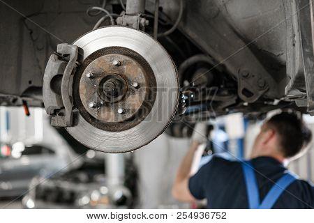 Car Mechanic Inspecting Car Wheel And Repair Suspension Detail. Lifted Automobile At Repair Service