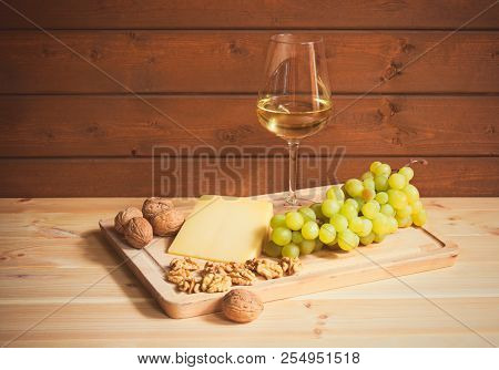 Glass Of White Wine, Parmesan Cheese, Walnuts  And Grape Branch On Wooden Table