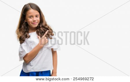 Brunette hispanic girl cheerful with a smile of face pointing with hand and finger up to the side with happy and natural expression on face looking at the camera.