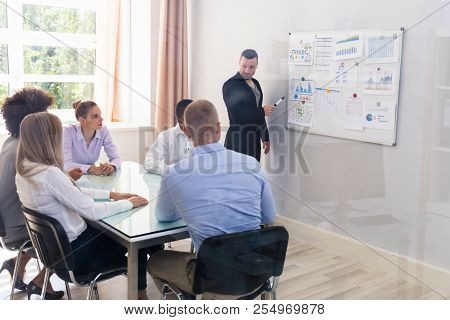 Young Businessman Explaining Graphs To His Colleagues At Workplace