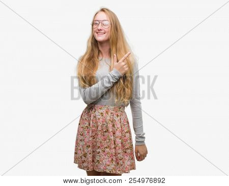 Blonde teenager woman wearing flowers skirt cheerful with a smile of face pointing with hand and finger up to the side with happy and natural expression on face looking at the camera.