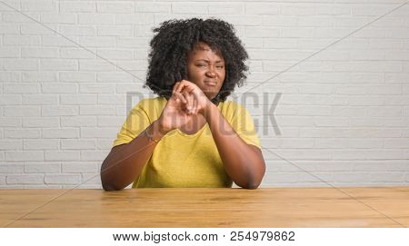 Young african american woman sitting on the table at home disgusted expression, displeased and fearful doing disgust face because aversion reaction. With hands raised. Annoying concept.