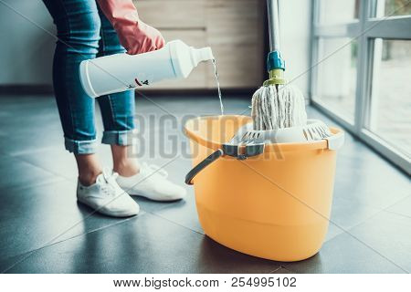 Woman In Gloves Prepearing To Wipe Floor With Mop. Closeup Of Girl Wearing Protective Gloves Mixing