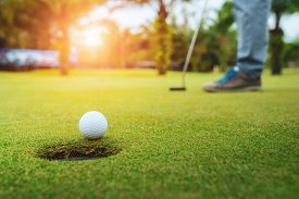 Golfer Putting Golf Ball On The Green Golf, Lens Flare On Sun Set Evening Time, Pro Golf Long Puttin