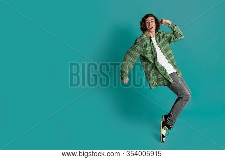 Cheerful Young Man Standing On Tiptoes Against Color Background, Blank Space