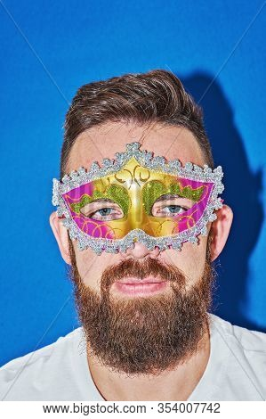 Closeup Portrait Of Man In Mardi Gras Masquerade Mask In Complementary Art. Funny Face During Celebr