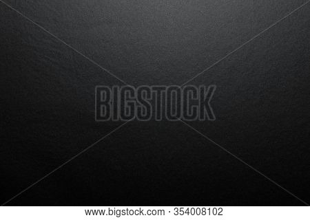 Black Background Made Of Real Black Paper With A Matt Fibrous Structure, Illuminated By A Soft Light