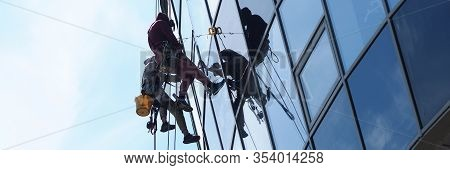 People Professionally Work At Height Wash Windows. Wash The Windows Outside On High Floor. Professio