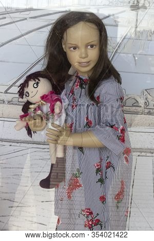 Mannequin Little Creepy Girl In A Dress And With A Doll In Her Hands