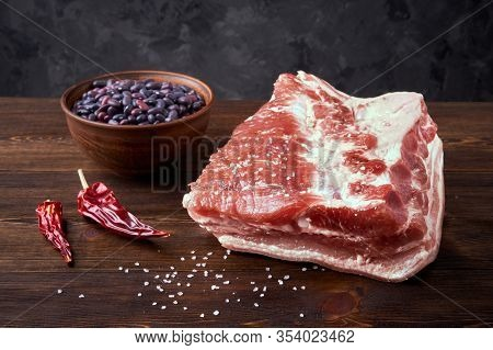 Raw Pork Belly And Red Beans On A Dark Wooden Brushed Background. Spices: Hot Peppers, Salt. Rustic