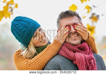 Portrait of beautiful woman covering her husband eye in park