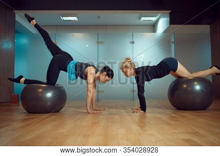 Two girls, pilates training with balls in gym