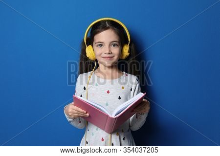 Cute Little Girl With Headphones Listening To Audiobook On Blue Background