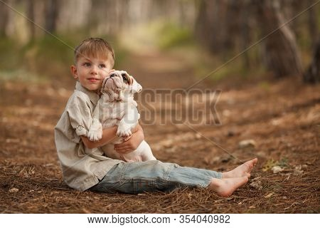 Cute Baby Boy Hugs And Plays His Funny English Bulldog Puppy On A Walk In The Park, Beautiful Portra
